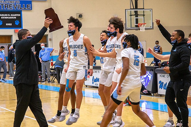 Reece Schirmer and his Centreville teammates celebrate while Centreville Coach Kevin Harris holds up the Class 6 Trophy after his team defeated Potomac 63-49.
