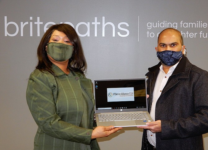 Britepaths client Alicia Salmon receives her new laptop from Anil Atyam, whose company is part of ITServe Alliance.