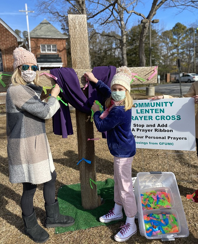 Sandra Musser and her daughter Caroline tie small ribbons noting their prayer intentions to the community Lenten Prayer Cross at United Methodist Church in Great Falls.