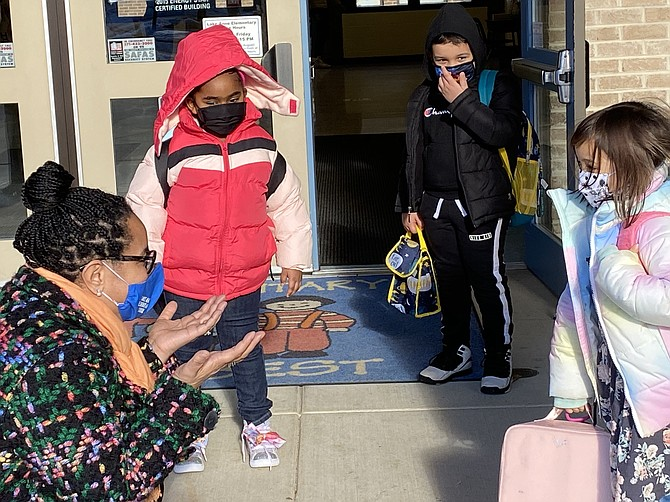 Principal Jill Stewart at Lake Anne Elementary School in Reston talks with children as they arrive for their first day of in-person learning at the school.