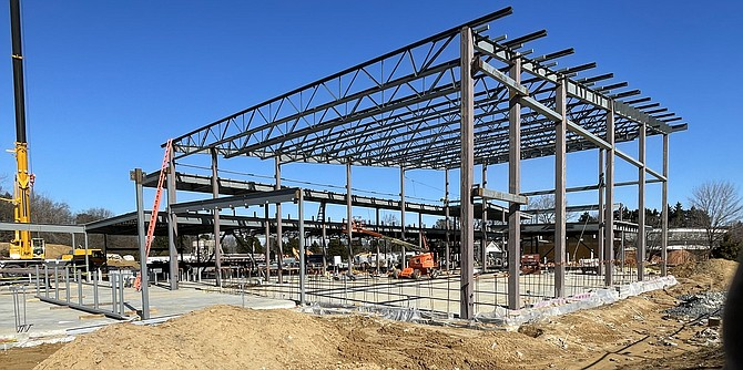 Steel beam outlines of the new Lorton community center dwarf the old library (right rear).