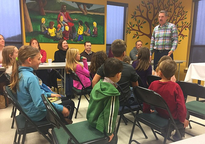 The Rev. Rob Bromhead speaks to children and parents at a CPC Communion Workshop.