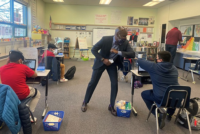 Alexandria City Public Schools Superintendent Gregory Hutchings gives an elbow bump greeting to a student March 2 at Mount Vernon Community School. ACPS students returned to in-person classes after nearly a year of virtual learning due to the COVID-19 pandemic.