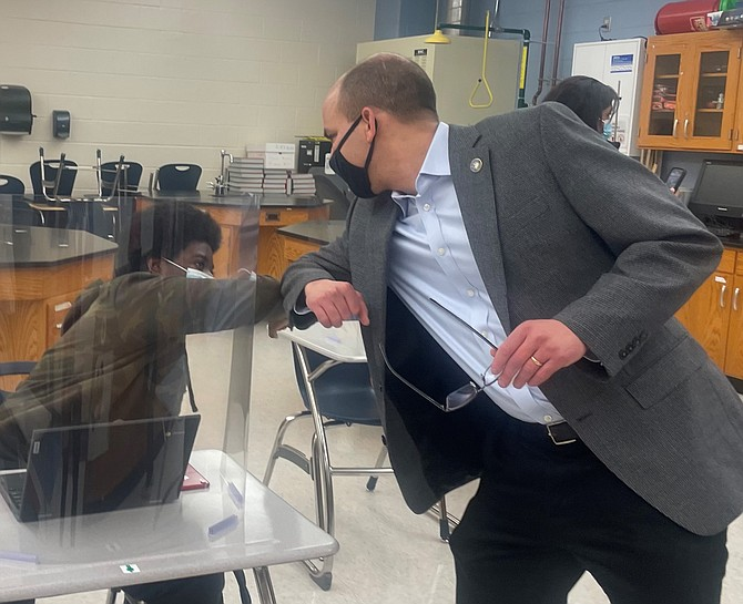 Alexandria Mayor Justin Wilson gives an elbow bump greeting to a student in the honors earth science class at T.C. Williams High School March 16.