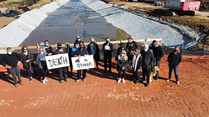 Vienna and Great Falls residents stand with their back to Colvin Run after the Virginia Department of Transportation realigned the waters into a paved trapezoidal channel near the confluence with Difficult Run as part of its Route 7 Improvements.