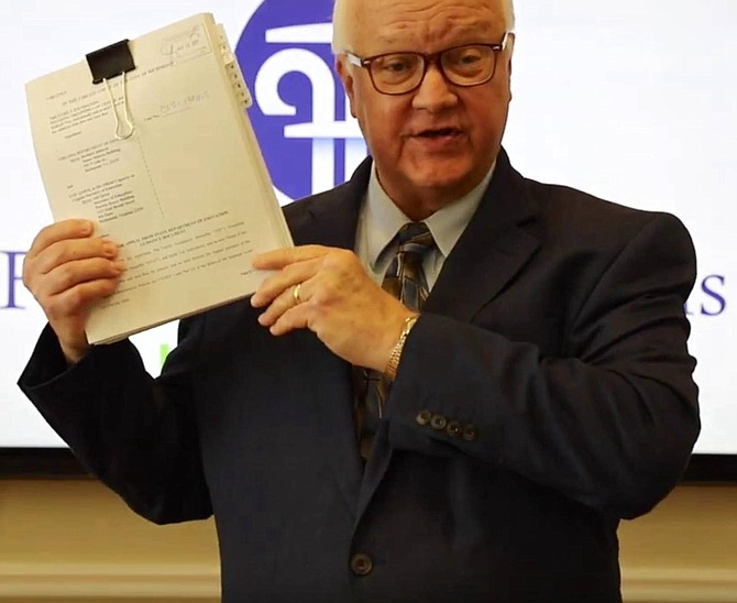 Jim Davids, Chief Counsel of the Founding Freedoms Law Center, holds up the 30-page lawsuit.