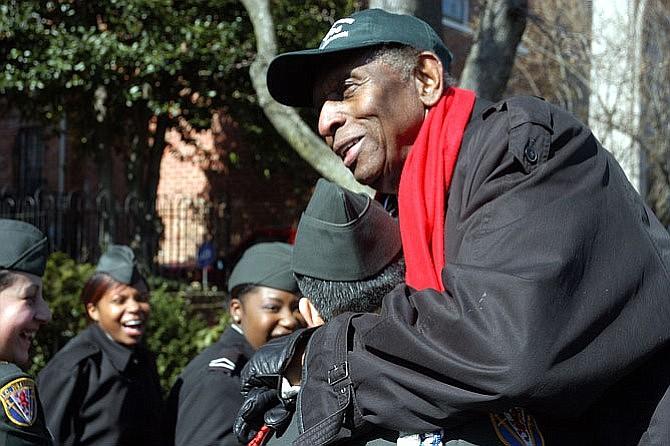 Earl Lloyd, serving as the 2006 George Washington Birthday Parade grand marshal, talks with members of the T.C. Williams JROTC program before the start of the parade.