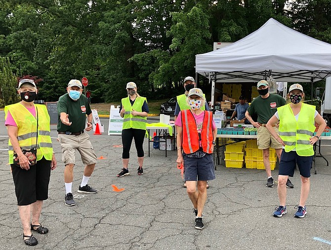 Volunteer team  manages Reston Farmers Market with Covid protocols.