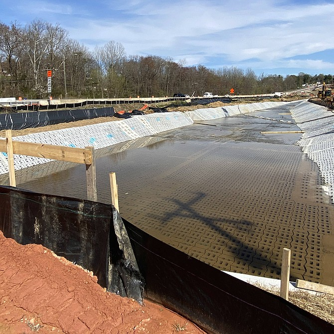 Colvin Run as an articulated concrete block channel with the addition of staggered weirs, wooden boards to dissipate the water velocity.