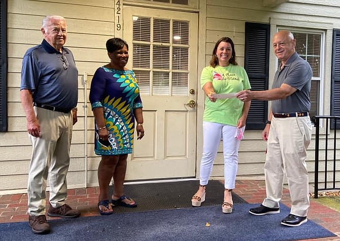(From left) Rotary Club of Fairfax New Generations Director, Verne Tuininga, and Fairfax City Schools Superintendent Phyllis Pajardo look on while Kate Malesky of a Place to Stand receives a financial donation from Rotary Club of Fairfax President Barry Gordon.