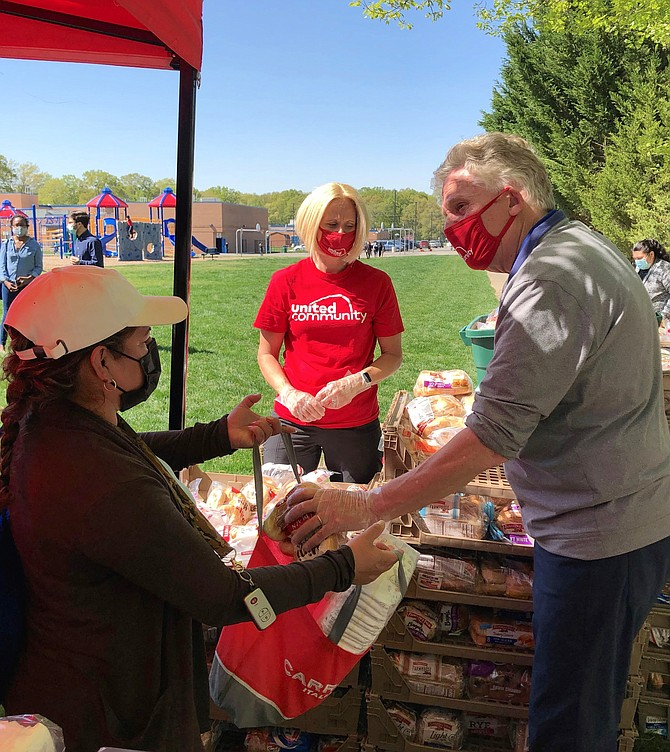 Former Virginia governor Terry McAuliffe, right, visits Mount Vernon Woods Elementary School April 20 during a United Community COVID relief food distribution event. McAuliffe is vying to win the Democratic nomination for governor on June 8.