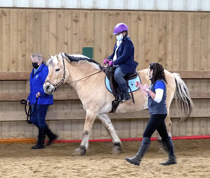 Conley takes a lesson on Finn with instructor Maya Grigorovich-Barsky (right) and LiftMeUp! Executive Director Georgia Bay (left).
