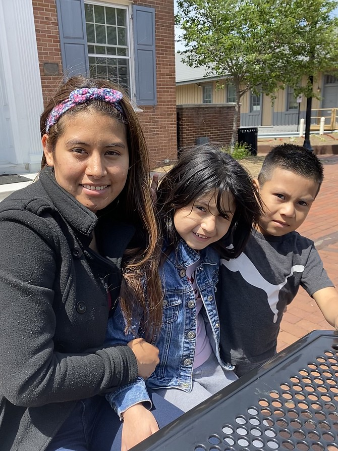 """(From left) Kenci Santamaria of Herndon, her daughter, Jaritza Santamaria, 9, and son, Jefferson Jose, 6, enjoy Mother's Day on the Town Square in front of the Old Town Hall in Herndon. Jaritza Santamaria, 9: """"Mom plays with me and takes me to the mall."""" Jefferson Jose, 6: """"I like Mom's eggs."""""""