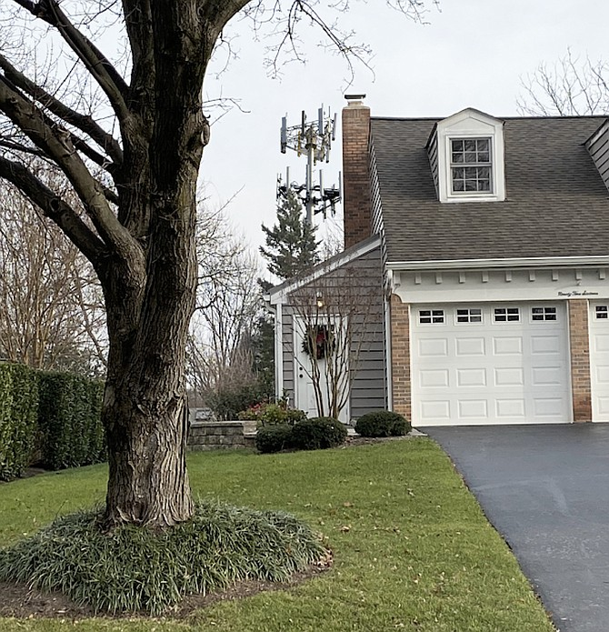 The photo illustration depicts the planned 114-foot telecommunications monopole tower. A proposed alternative could have been a 122-foot-tall tree pole monopine tower, with an additional 8 feet of faux tree branches. According to the homeowner near the corner of Bent Creek Lane and Stone Meadow Way in Vienna, the tower would have been visible to the left of the garage.
