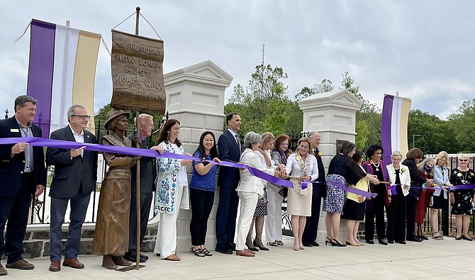 """Association members, NOVA Parks Board members, State legislators, and County Supervisor cut the Turning Point Suffragist Memorial ribbon in front of the entrance replicating the White House gates where suffragists maintained their """"silent sentinel."""""""