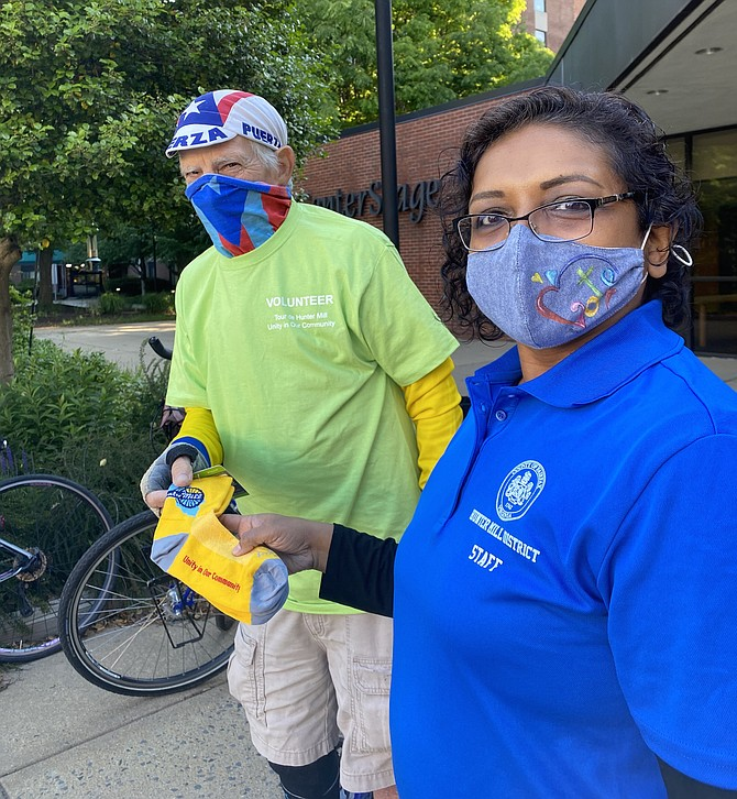 """Shyamali Hauth, Hunter Mill District Staff, hands volunteer Bob Evans, senior W&OD Trail patroller and Tour de Hunter Mill ride marshal, a colorful pair of """"Unity in Our Community"""" cycling socks, sure to step up the style of his cycling game."""