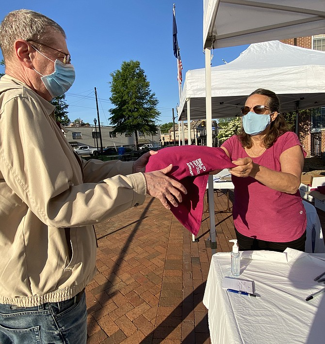 Cindy Roeder, the Herndon Parks and Recreation Director, hands David Agland of Herndon his official t-shirt at the Herndon Pit Stop in front of the Old Town Hall and Train Depot.