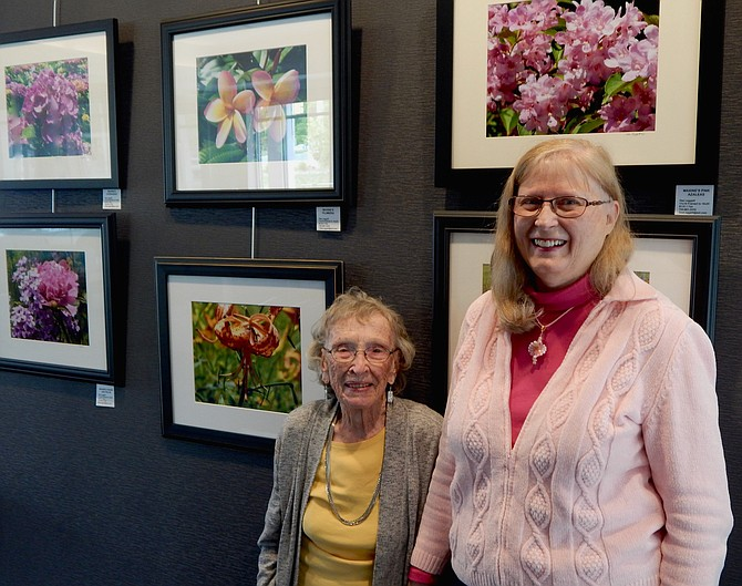 Maxine Turner and Dee Leggett in front of the display of Maxine's flower photographs at TD Bank in Great Falls.