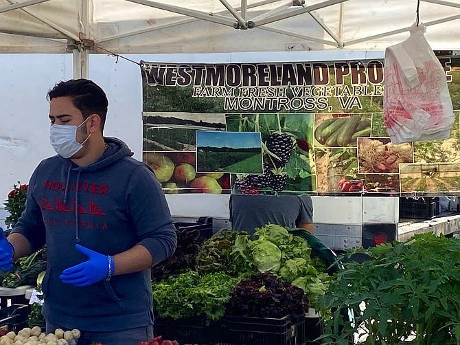 Francisco Becerra of Westmoreland Farms moves quickly, selling fresh produce, collards, asparagus, mushrooms, and plants at the vendor stand.