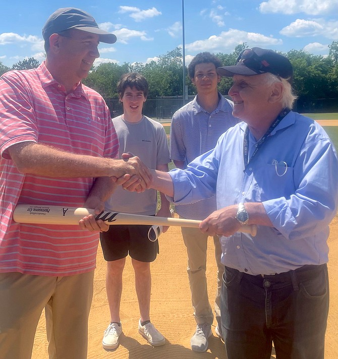 Donald Dinan, right, congratulates Frank Fannon as the new majority owner of the Alexandria Aces May 15 at Frank Mann Field. Looking on are front office staff Mitch Wasserman and Zach Miller.