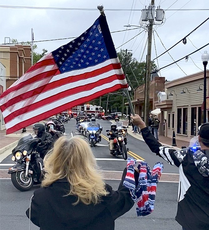 Three members of the Town of Herndon Police Motorcycle Squad lead the Jimmy's Tavern Memorial Day motorcycle convoy down Spring Street, turning onto Elden Street where Town Mayor Sheila Olem waves her red, white, and blue scarf, and Joshua Jay waves a large United States flag bidding them a safe journey to Washington, D.C. for the Rolling to Remember ride 2021.