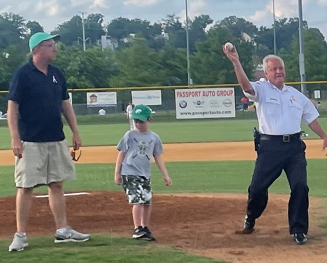 Sheriff Dana Lawhorne, right, throws out the ceremonial first pitch at the opening game for the Alexandria Aces June 8 at Frank Mann Field. Lawhorne is joined on the mound by his grandson Ryan Kaskela and Aces owner Frank Fannon.