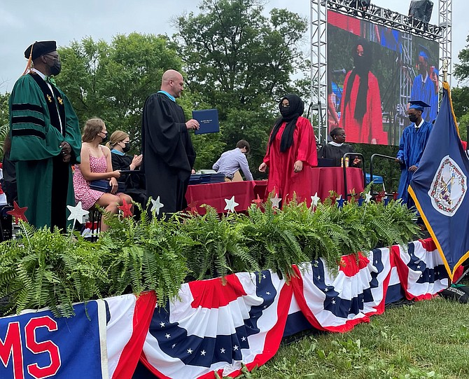 ACPS Superintendent Dr. Gregory Hutchings, left, and T.C. Williams High School principal Peter Balas present diplomas to the Class of 2021 during commencement ceremonies June 12 at Chinquapin Park.