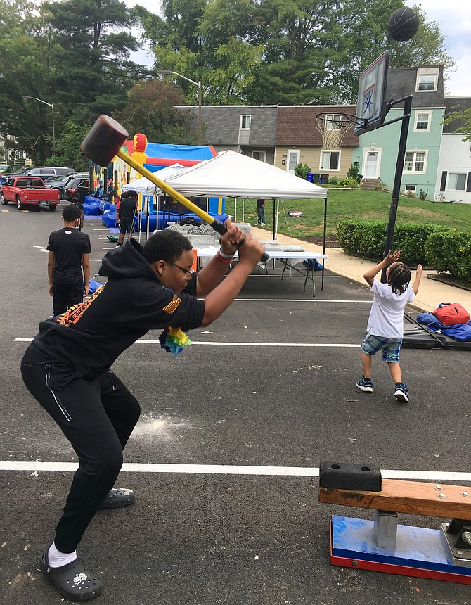 """Kristopher Paul, 15, tests his strength at the Scotland Juneteenth celebration Saturday. Paul rings the bell, designating him a """"Thunder God."""""""