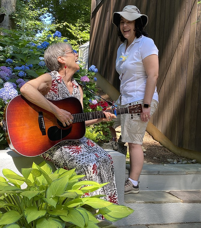 (From left) Reston Chorale members, Nancy Riley of Oak Hill and Melissa Cyrulik of Potomac, Md., enjoy a moment together before ticketed participants in the Gardens of Note 2021 tour arrive at the residential garden of Cindy Brown and Chuck Daoud.