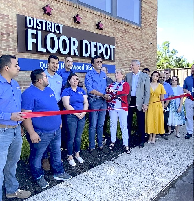 (Center) Managing Partner of District Floor Depot Yusef Mehmetoglu steadies the giant ribbon-cutting scissors with Town of Herndon Mayor Sheila Olem for the Ceremonial Grand Opening of the business after its soft-opening in the fall of 2020.