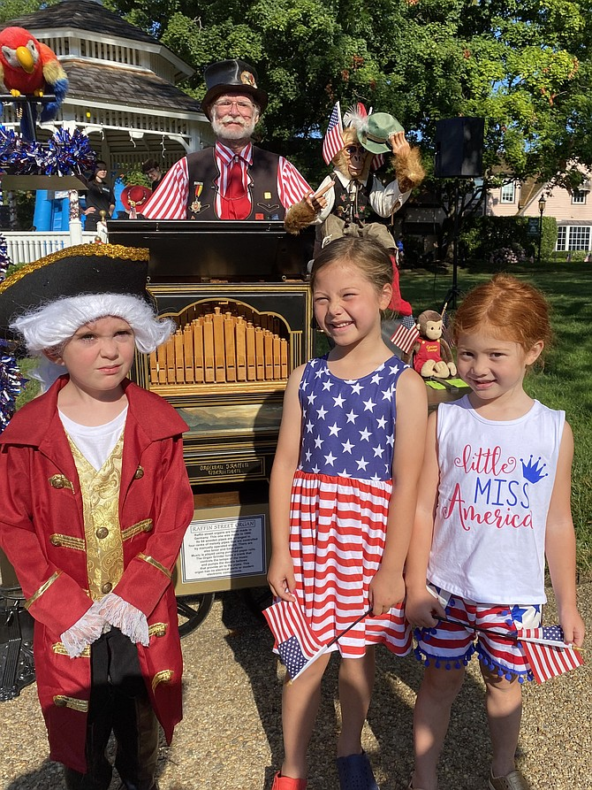 John Maloney, 5, of Great Falls, joins Ella DeTrani, 6, of McLean and her sister, Lia, 5, after listening to Terry Bender of Great Falls explain how the organ grinder plays music.
