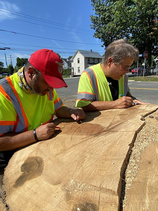 (From left) Victor Lopes, Elden-Center Streets Intersection Improvements Project manager, and John Dudzinsky, Herndon Town Forester, begin counting the growth rings on the Overcup Oak Tree that was struggling as evidenced by signs of disease. It obstructed the approach sight triangle quadrant to the four-legged intersection, causing a vehicular, pedestrian, and cycling safety concern.