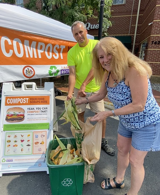 With a little assistance from Fritz Gottschalk of Veteran Compost, Sarah McGuire of Herndon drops her food scraps in the container at the Herndon Farmers Market location, one of four county markets selected to test the food scrap composting program.