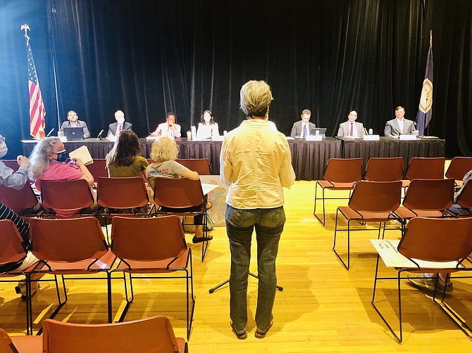 Members of the redistricting commission listen to Debora Wake, president of the League of Women Voters of Virginia, during a public hearing this week at George Mason University.