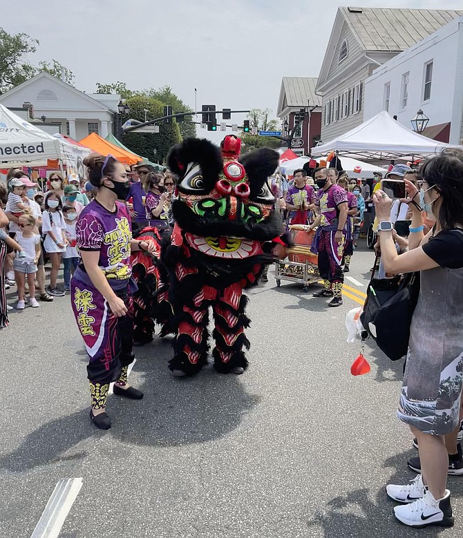 Chinese Lion dances up Main Street collecting tribute and head pats.