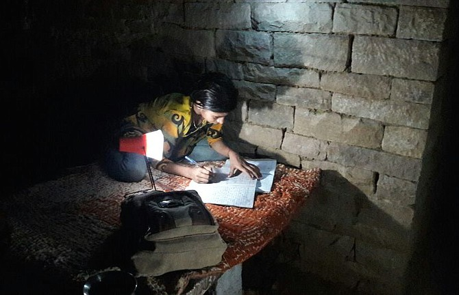 A young girl from Chikulia village in Uttar Pradesh studying at night with the family's new solar lantern.