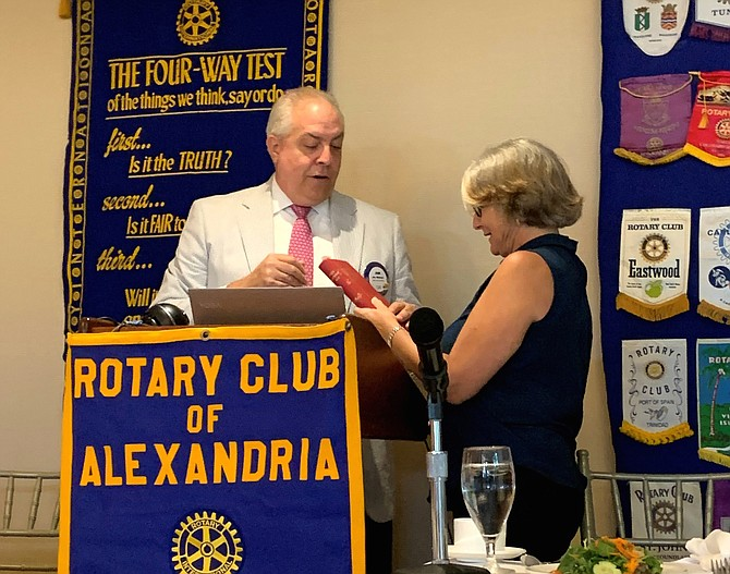 John Moorman, left, presents Alexandria Rotary Club president Pam De Candio with a 1935 edition of This Rotarian Age by Rotary founder Paul Harris during the organization's July 27 meeting at Belle Haven Country Club.