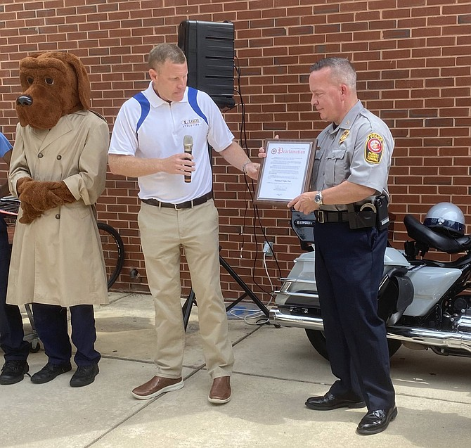 With McGruff the Crime Dog facing forward, Jeffrey C. McKay, Chairman of the Fairfax County Board of Supervisors, hands Kevin Davis, Chief of Police Fairfax County, the Proclamation by the Board of Supervisors on behalf of all residents of Fairfax County proclaiming Tuesday, Aug. 3, National Night Out.
