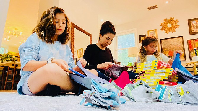 Senzel Schaefer, Afghan American, and her daughters, pack 100 small backpacks, each with a workbook, markers, and a set of clothes and socks for Afghan refugees. Later, the girls wrote letters to enclose.