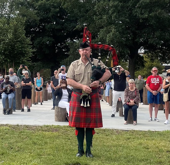 Crowds stand as a bagpiper plays Amazing Grace during the Waterfront Park ceremony remembering the victims of the Sept. 11, 2001, attacks.
