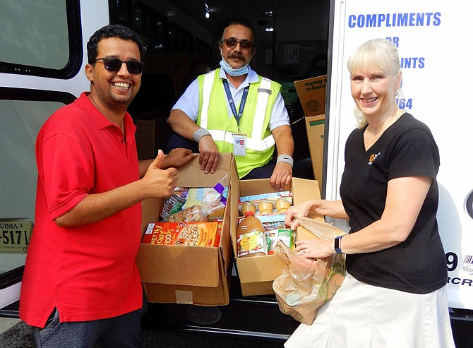 Several Stuff the Bus events were held in the local area on Sept. 11. Showing some of the food they collected at this one, in the Centreville Regional Library parking lot, are (from left) Yousef Alrajhi with Volunteer Fairfax, bus driver Saeid Khalighi and Sarah Barton with Western Fairfax Christian Ministries (WFCM), which received the items for its food pantry serving families in need in Centreville and Chantilly.