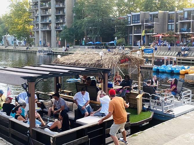 With multiple houseboats full of family and friends at Lake Anne's main dock, paddleboarders on SUPs head toward the remaining space to disembark and enjoy an evening of music.